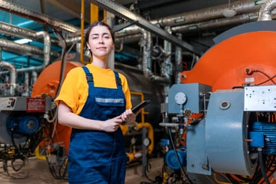 Young Female HVAC Technician in a Boiler Room